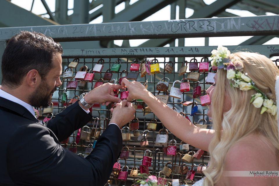 Michael Röhrig Hochzeitsfotograf - Brautpaar bringt Liebesschloss an der Hohenzollernbrücke an.